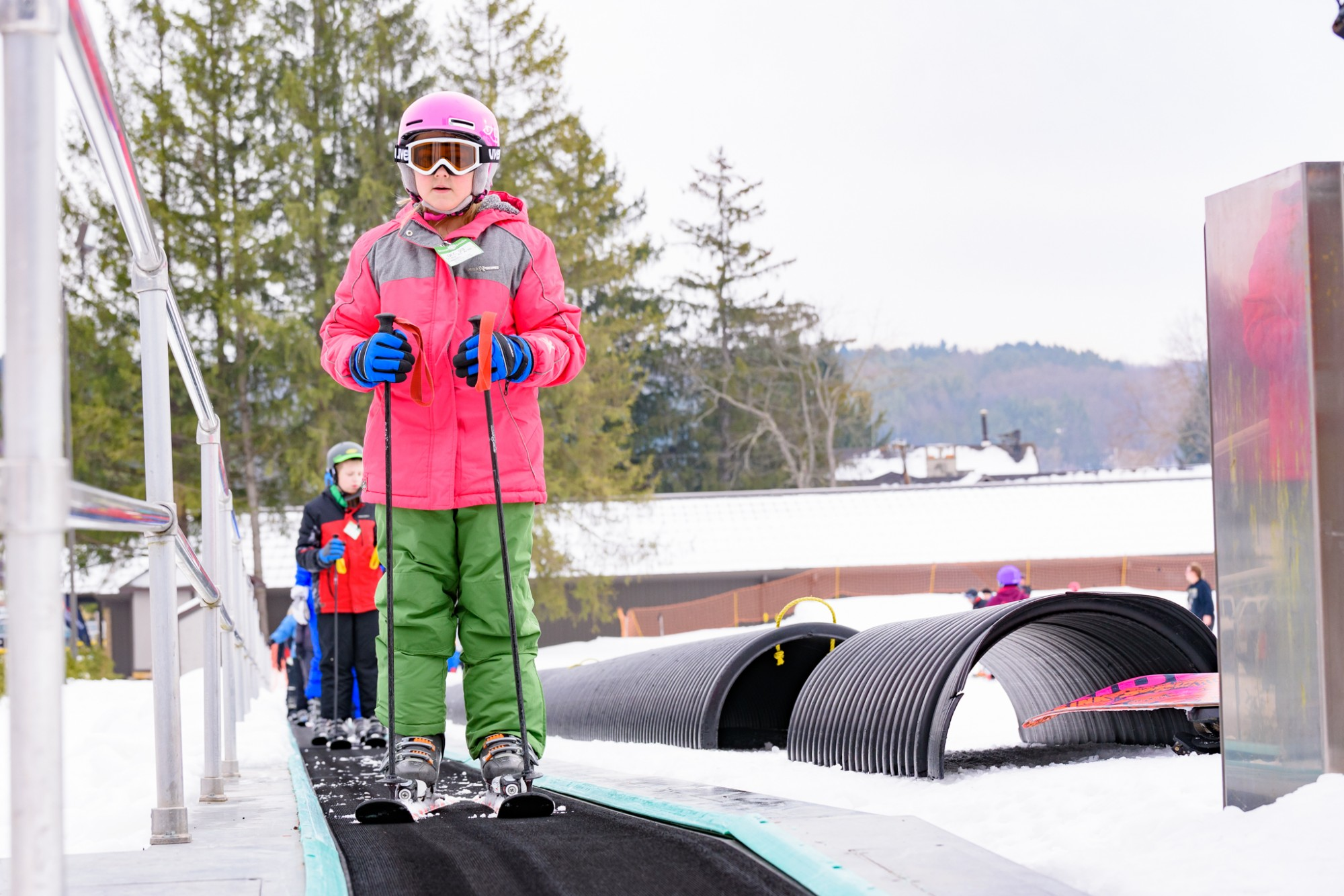 Young Skier on Conveyor Carpet Lift Ride at Snow Trails