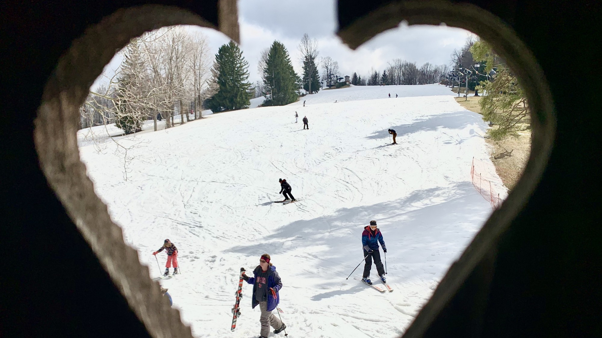 Looking through heart shaped railing at ski slope